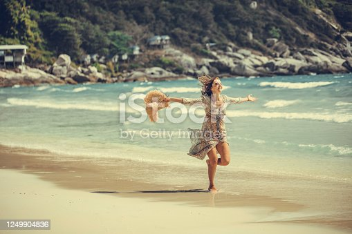 woman in a boho dress walking on the tropical beach