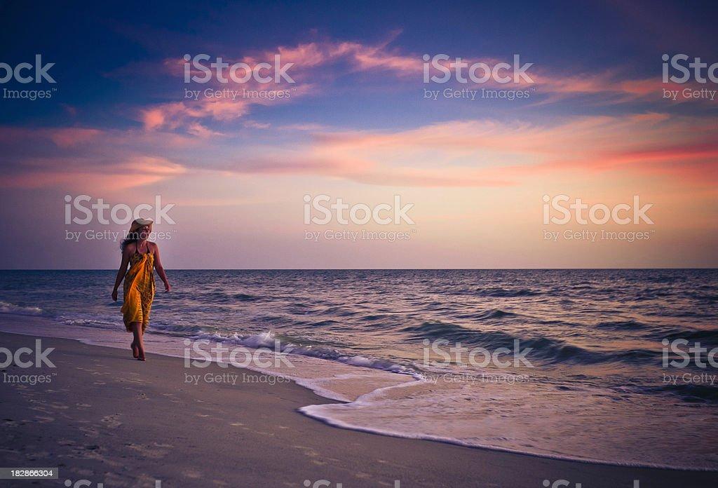 woman walking on the beach stock photo