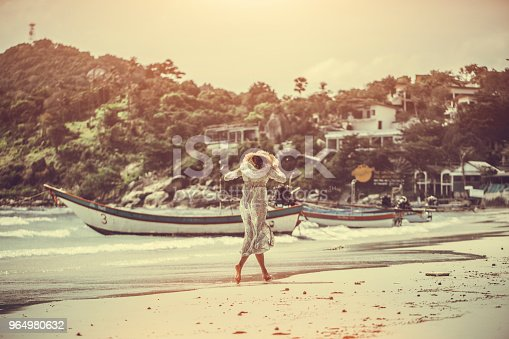 woman in a boho dress walking on the tropical beach