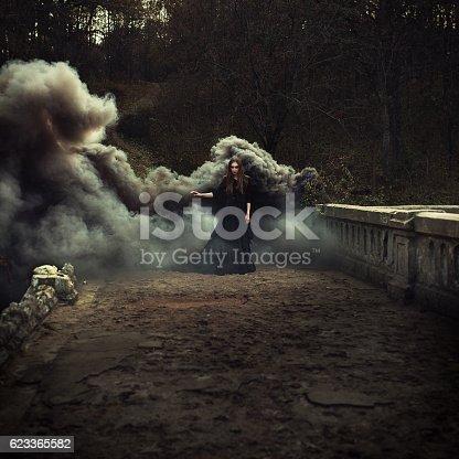 woman walking on the bridge in heavy black smoke. Like a witch