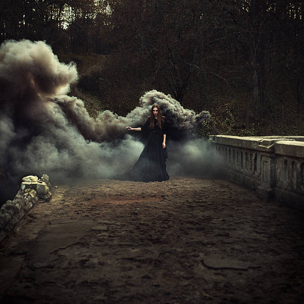 woman walking on the bridge in heavy black smoke - horror bücher stock-fotos und bilder