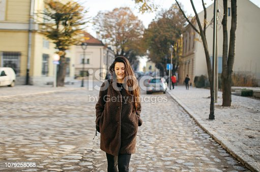 Young woman is having a morning walk on the empty streets of Belgrade, Serbia. She is enjoying the nice winter day, relaxing alone, wearing a casual fake fur coat, passing by the old town buildings from the '20s and '30s.