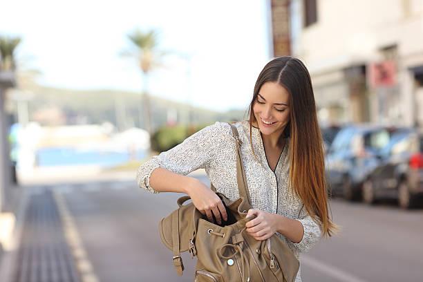 frau zu fuß auf der straße und auf der suche in einer tasche - leder handtaschen damen stock-fotos und bilder