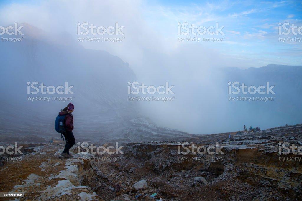 Woman walking on top of crater Mount Kawah Ijen volcano. stock photo
