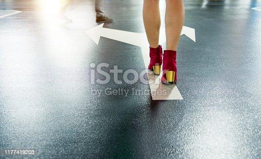 171150458istockphoto Woman walking on white direction arrow 1177419203