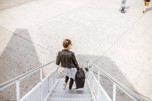 Woman walking out the airplane stock photo