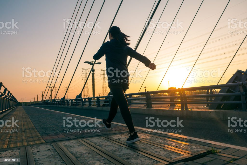 Woman walking outdoors with sunlight stock photo