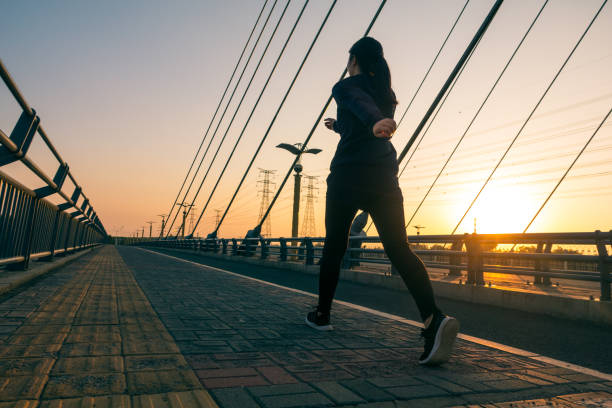 Woman walking outdoors with sunlight Woman walking outdoors with sunlight slow motion stock pictures, royalty-free photos & images
