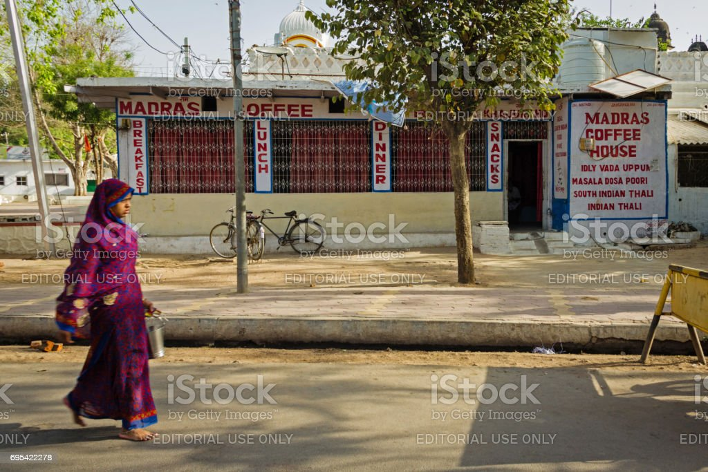 A woman walking pass Madras Coffee House in the morning stock photo