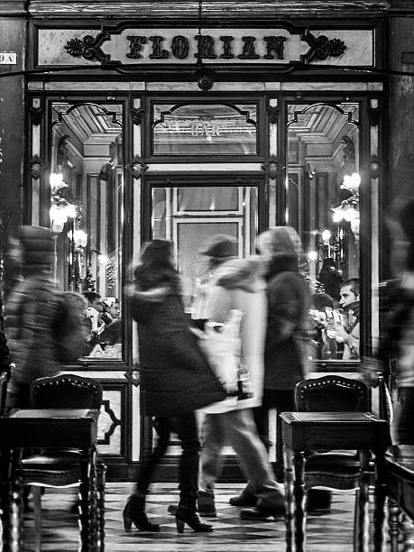 Woman walking past the Florian Caffe in St Mark's Square stock photo