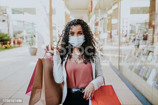 istock Woman walking shopping and Smiling behind the mask 1255197496