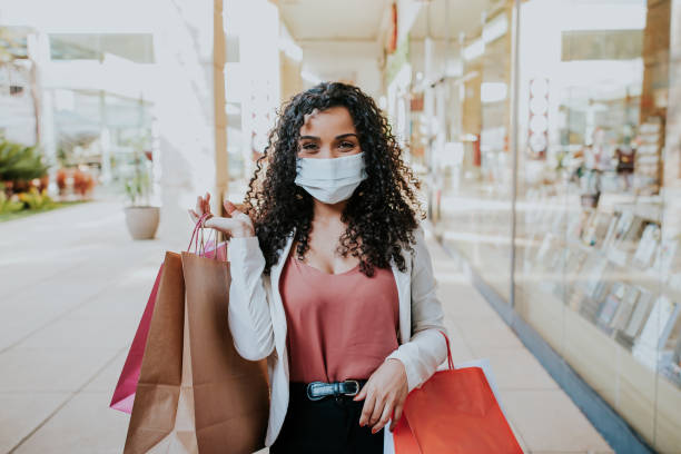 Woman walking shopping and Smiling behind the mask Woman walking shopping and Smiling behind the mask - new normal concept cheap stock pictures, royalty-free photos & images