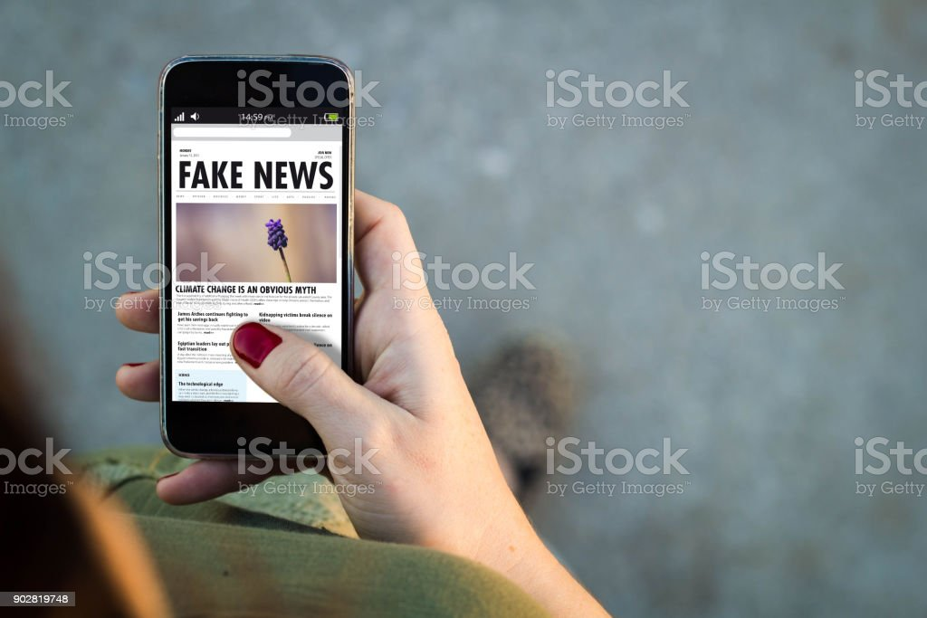 Woman walking smartphone fake news stock photo