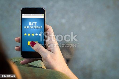 istock Woman walking smartphone rating on a web 539815226