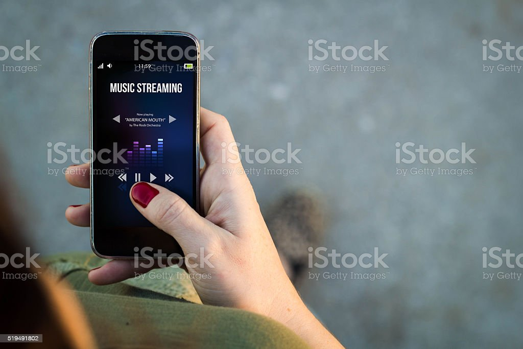 Woman walking smartphone with music streaminginterface stock photo