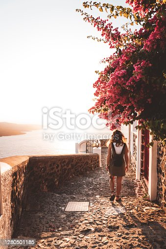 istock Woman walking the streets of Fira at sunset 1280501185