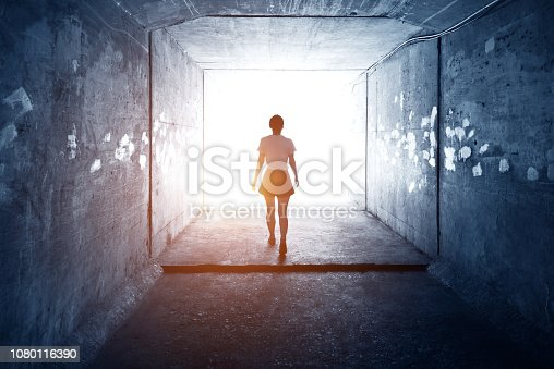 Woman walking through a dark tunnel.