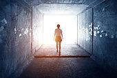 Woman walking through a dark tunnel.