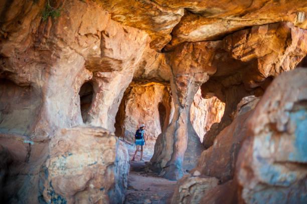 여자는 사암 동굴을 통해 걷고 - 생태 보전 지역 뉴스 사진 이미지