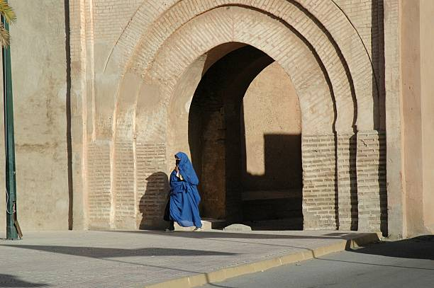 Woman walking through arch in Morocco stock photo