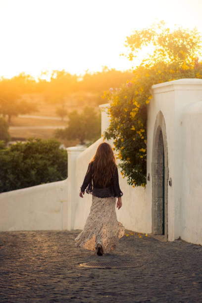 Woman walking through charming cobblestone street in the whitewashed town of Tavira, Portugal at sunset stock photo