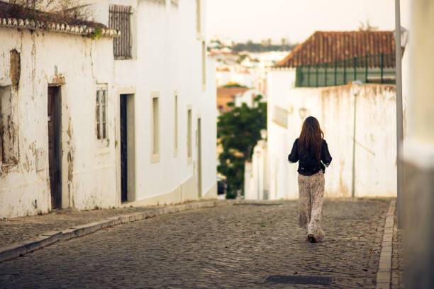 Woman walking through charming cobblestone street in the whitewashed town of Tavira, Portugal stock photo