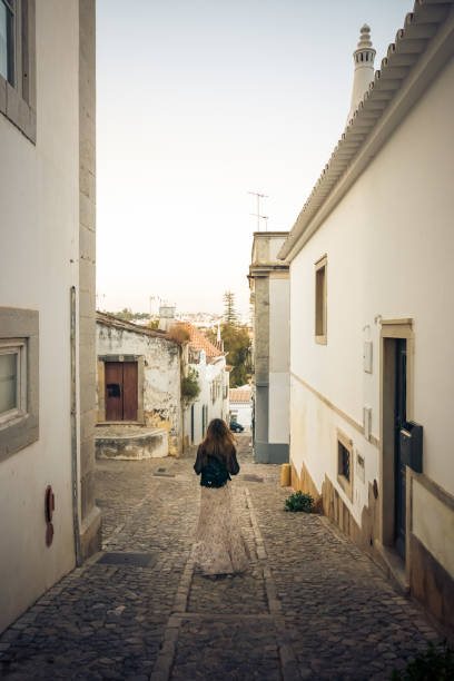 Woman walking through charming cobblestone street in the whitewashed town of Tavira, Portugal stock photo