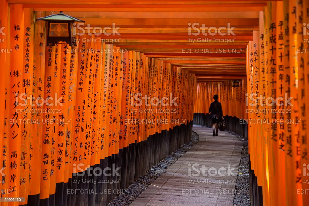 Woman walking through Fushimi Inari Shrine stock photo
