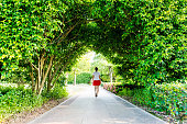 Woman walking through green natural tunnel.