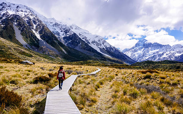 woman walking through hooker valley trail - nieuw zeeland stockfoto's en -beelden