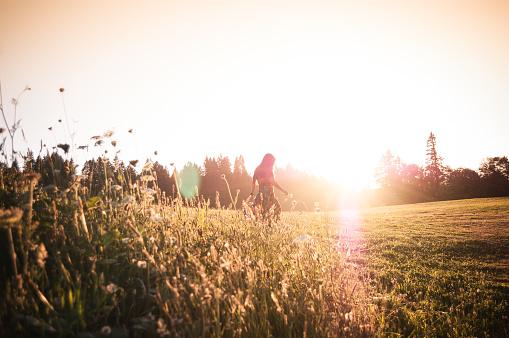 Woman walking through meadow at sunset
