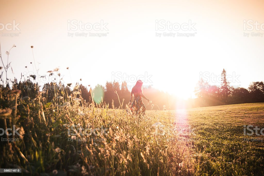 Woman walking through meadow at sunset stock photo