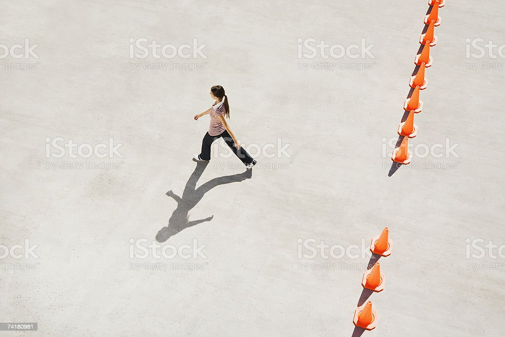 Woman walking through opening in row of traffic cones royalty-free stock photo
