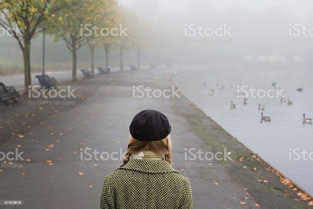 Woman walking through park stock photo