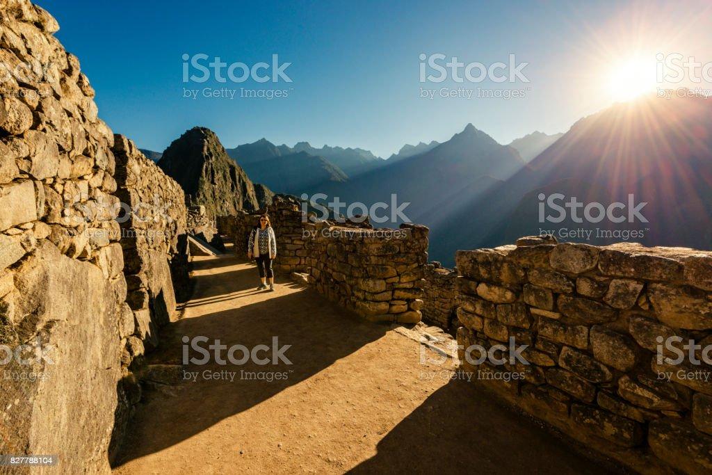 Woman walking through the Inca ruins of Machu Picchu stock photo