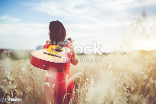 Young cheerful woman walking through the wheat field with guitar on back.