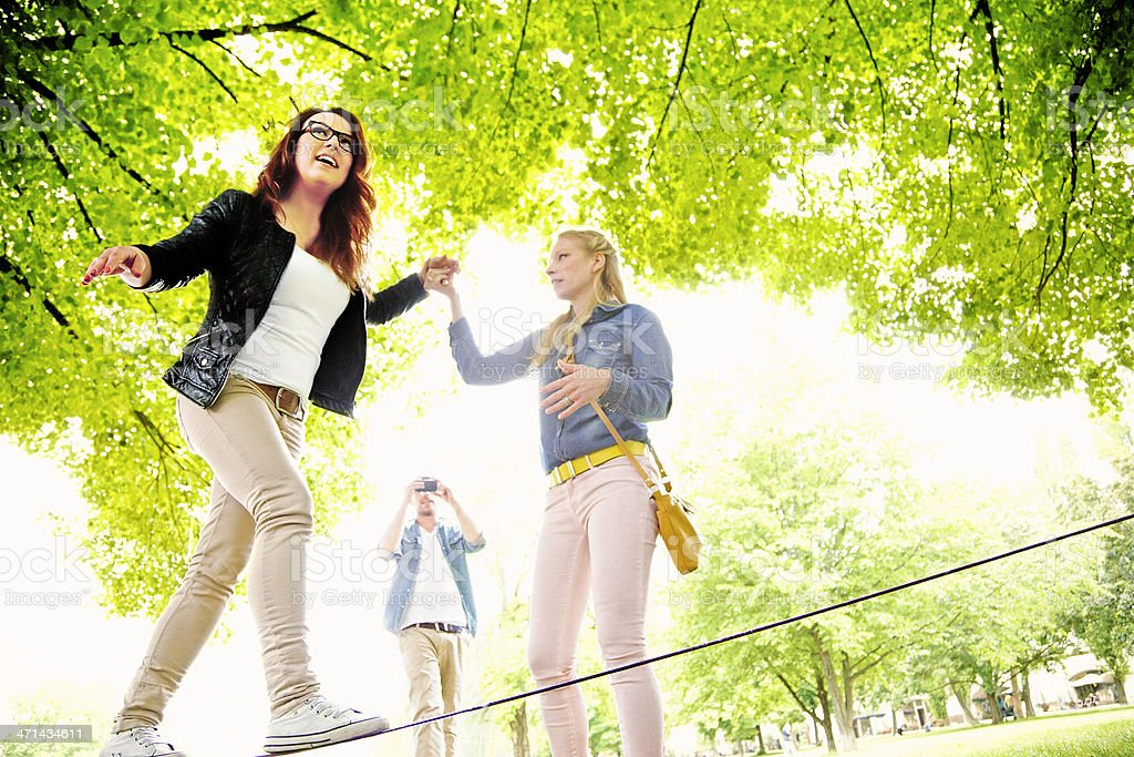 woman walking tightrope, assisted by friend royalty-free stock photo