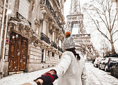 Woman walking to the Eiffel tower with snow