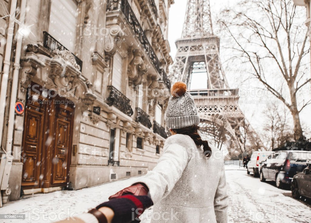 Woman walking to the Eiffel tower with snow stock photo