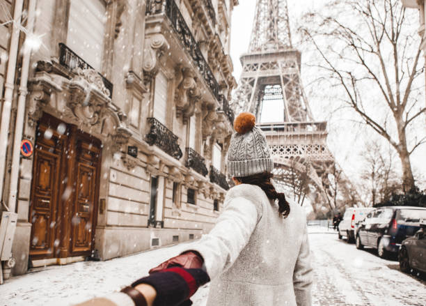 woman walking to the eiffel tower with snow - париж франция стоковые фото и изображения