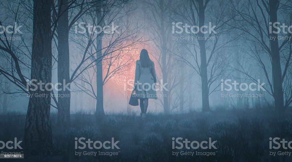 Mulher caminhando em direção de incandescência símbolo alienígena na floresta à noite - foto de acervo