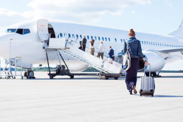 Woman walking towards the airplane Rear view of young woman with luggage walking towards the airplane. Female traveler going on vacation passenger stock pictures, royalty-free photos & images