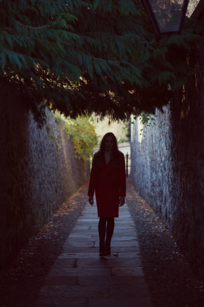 Woman walking towards us up a dark alley stock photo
