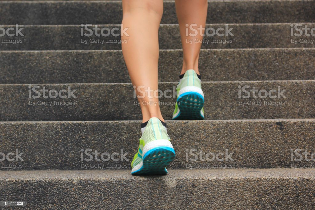 Woman walking up the stairs, Fitness woman legs running and burn fat in the body, Healthy lifestyle concept stock photo