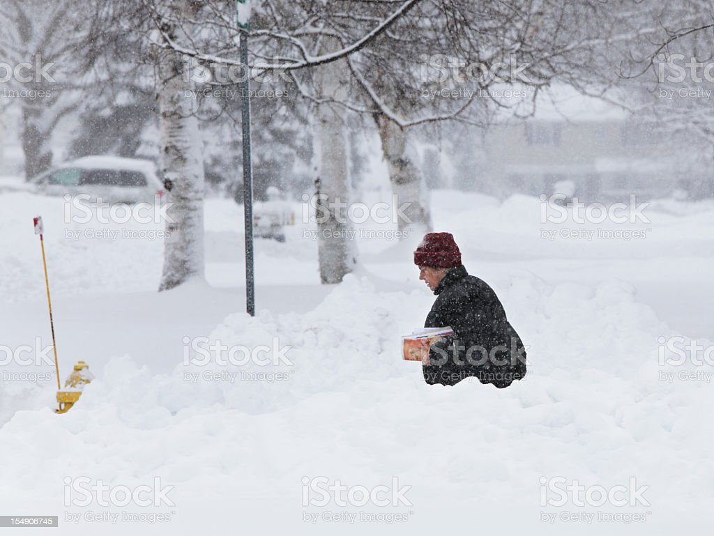 Woman Walking Warmly Dressed Carrying Magazine Mail During Blizzard Snow royalty-free stock photo