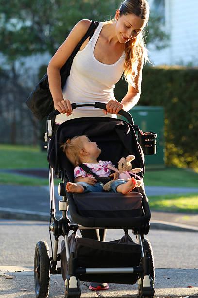 Mujer caminar con cochecito para niños - foto de stock