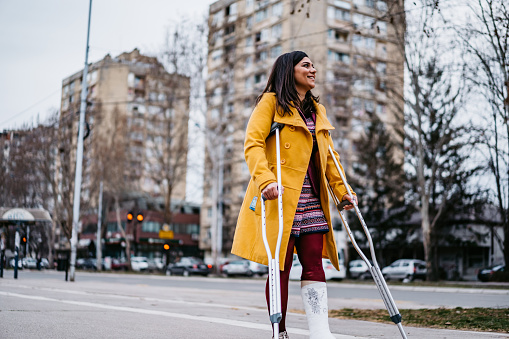 Woman with cast on foot walking with crutches.