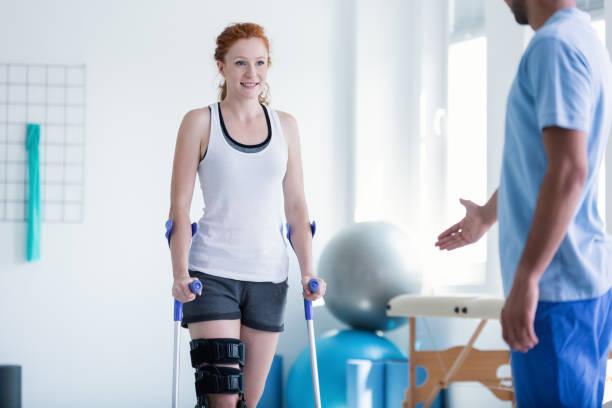 mulher andando com muletas durante a fisioterapia - ortopedia - fotografias e filmes do acervo