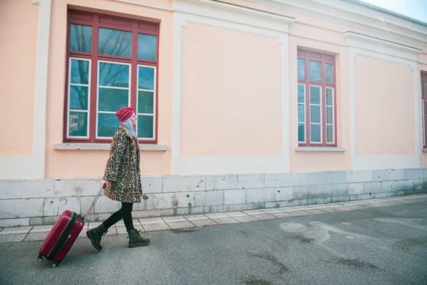 スーツケースを持って歩いている女性 - showus ストックフォトと画像