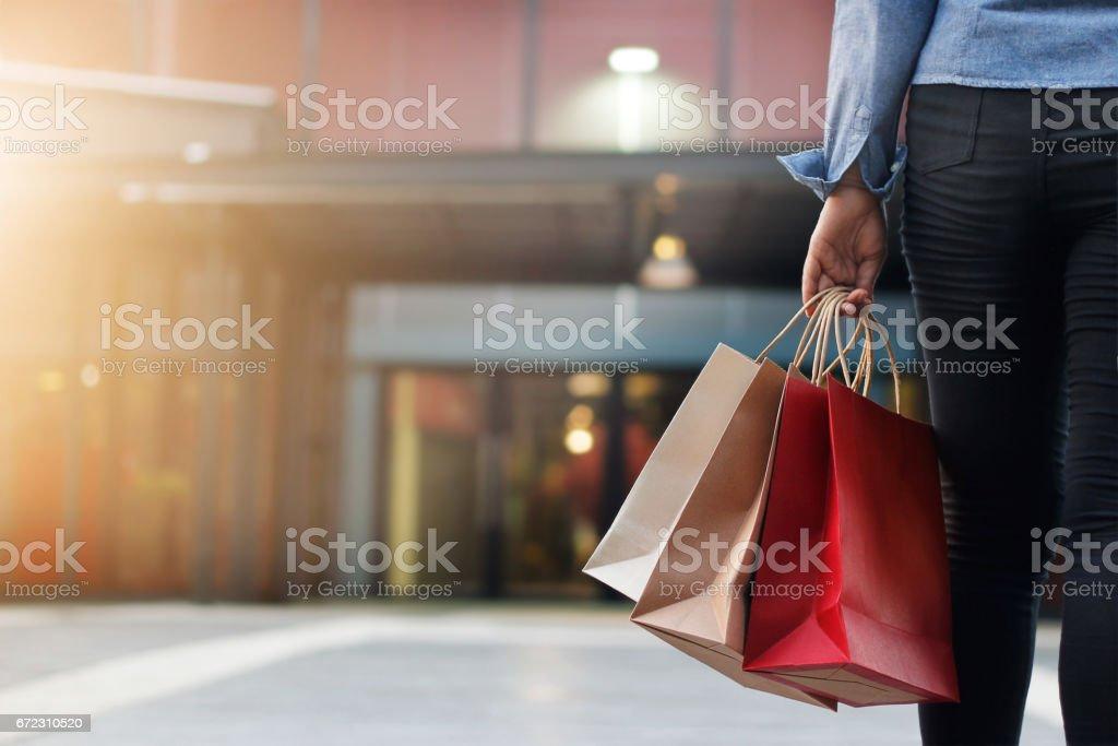 mujer caminando con bolsas de compras en centro comercial fondo - foto de stock